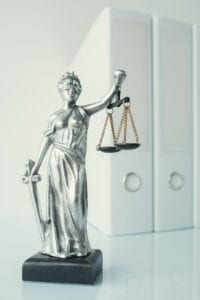 Lady Justice statue with document ring binders in law office